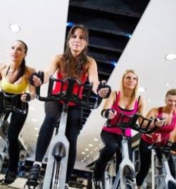 des femmes qui font une séance de spinning bike dans un gymnase